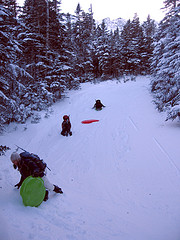 Image sledding on a snowy hill.