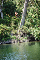 Picture of a man swinging on a rope over a river.