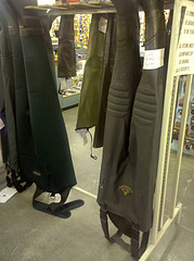 Image of waders hanging on a store rack.