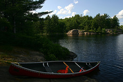 Image of a canoe beached on a rocky shore at a remote lake.